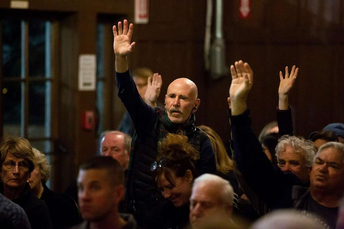 Ralph Somack, an Oakland resident, and others raise their hands t ask questions during a public hearing to discuss the three year Oakland Paving Plan followed by a Q&A for residents in Oakland, Calif. on Thursday, March 28, 2019.