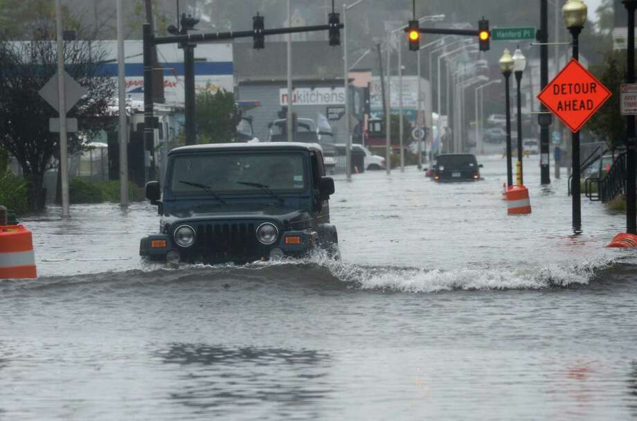 Motor vehicles try to make it through a closed Water Street after extreme hig tide and storm surge flooded coastal areas Saturday, October 27, 2018, in Norwalk, Conn. The Common Council's Health, Welfare and Public Safety Committee is looking to team up with the Public Works Committee to address flooding in the city. Photo: Erik Trautmann / Hearst Connecticut Media / Norwalk Hour