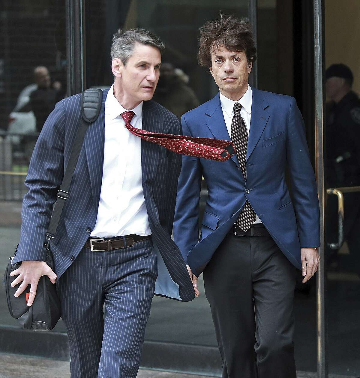Agustin Huneeus, right, a 53-year-old San Francisco resident whose family owns vineyards in California's Napa Valley and in Oregon, leaves the federal courthouse after a hearing associated with the college admissions bribery scandal, Friday, March 29, 2019 in Boston. Huneeus is accused of paying at least $50,000 to have SAT administrators correct his daughter's college entrance exam and to have USC officials designate her as a water polo recruit. (Matt Stone/The Boston Herald via AP)