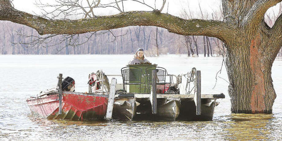 A man drives his small pontoon boat, with a jonboat tied along side, through flooded lower areas of Grafton Wednesday where the only way out to the Grafton Marina was by boat.