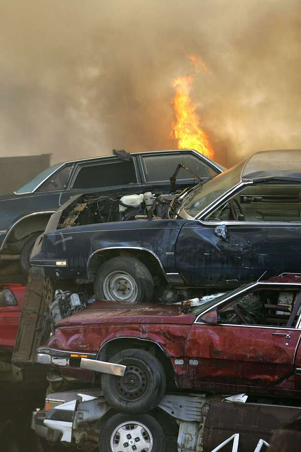 Flames shoot out from below stacked junked cars at a large industial fire at Smith's Salvage scrap metal yard Tuesday, Nov. 29, 2005 in Mobile, Ala. Workers were torching cars for metal when the blaze broke out and spread rapidly to a majority of the yard, engulfing old automobiles. (AP Photo/The Mobile Register, John David Mercer) Photo: JOHN DAVID MERCER / AP / THE MOBILE REGISTER