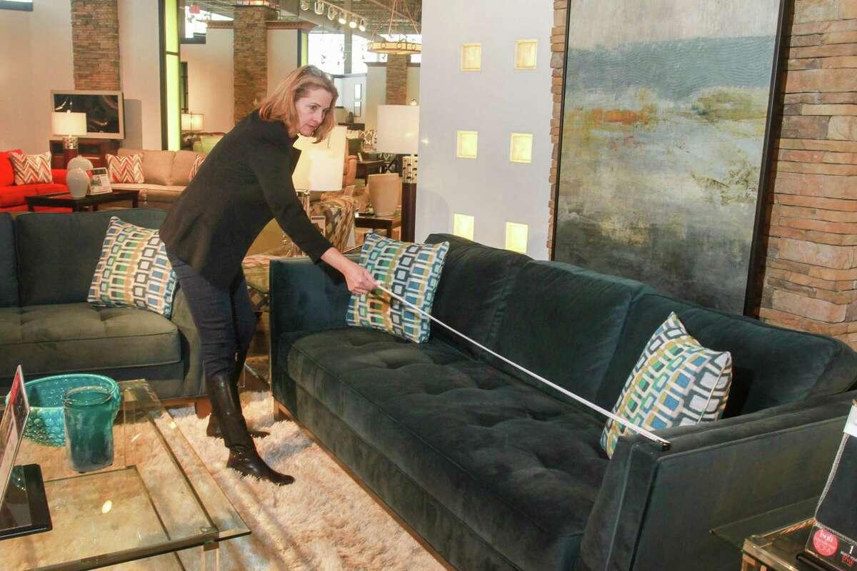 Laurel D'Antoni measures a sofa at Rooms To Go.