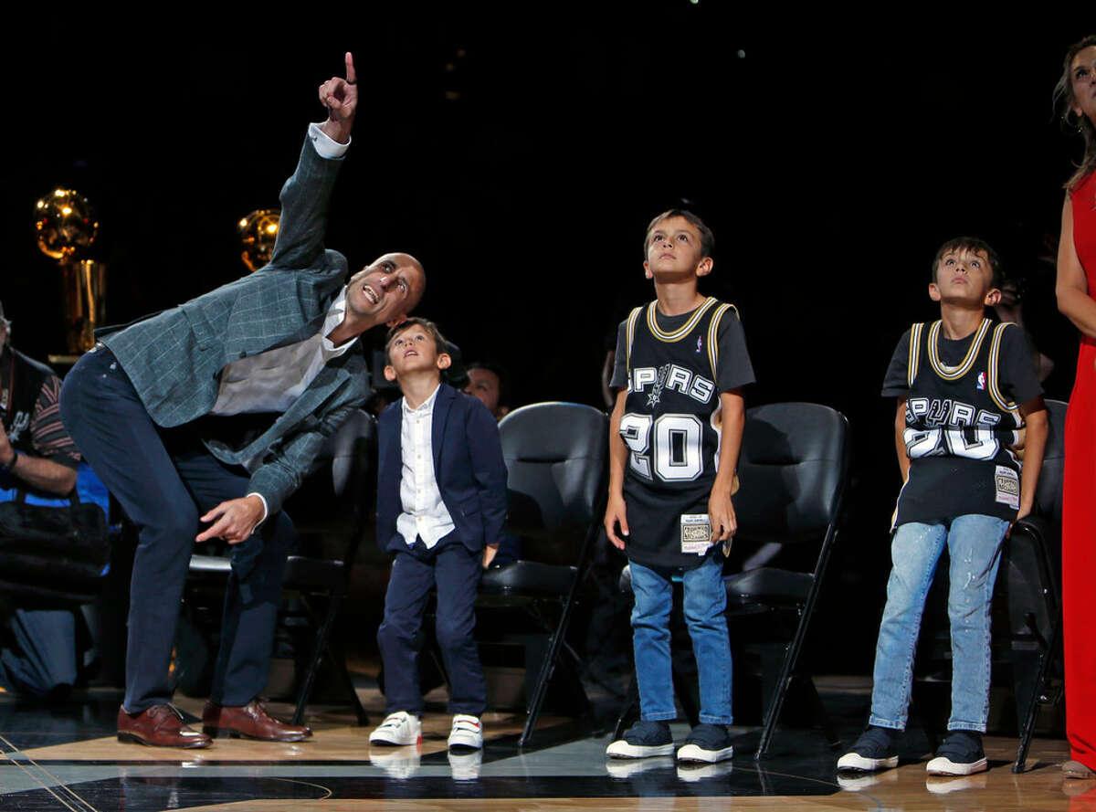 Manu Ginóbili muestra a su hijo menor la camiseta número 20 retirada por los Spurs en una ceremonia el jueves 28 de marzo de 2019 en el AT&T Center de San Antonio, Texas.