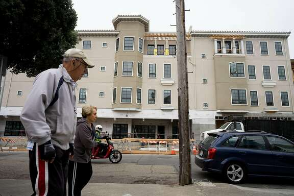 People walk past the Alexandria luxury condos in San Francisco Calif., on Tuesday, Sept. 4, 2018.