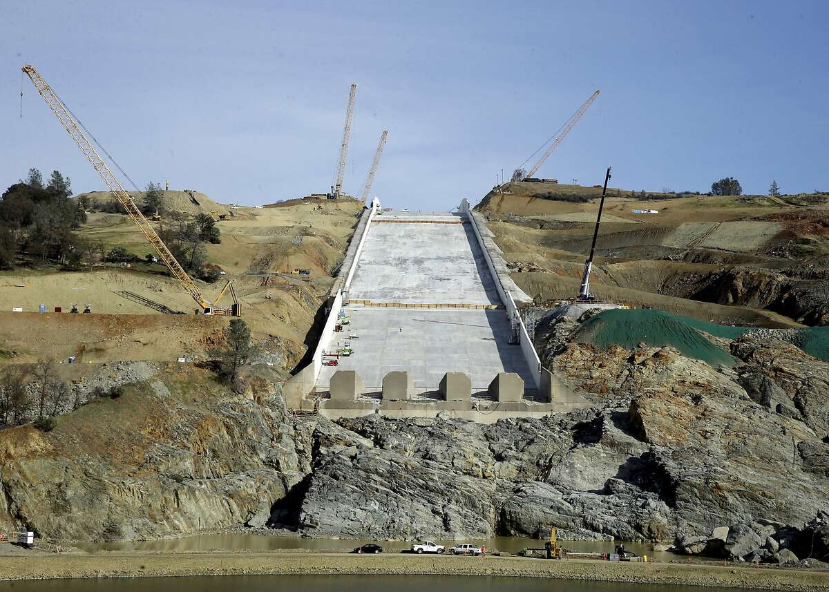 FILE - In this Nov. 30, 2017, file photo, cranes sit on the sides of the Oroville Dam spillway in Oroville, Calif. The federal government has rejected $306 million in reimbursements for California's repair of damaged spillways on the nation's tallest dam, a state agency said Friday, March 8, 2019. California has so far requested about $639 million from the Federal Emergency Management Agency for the Oroville Dam repairs, said Lisa Lien-Mager of the state's Natural Resources Agency. FEMA has agreed to cover $333 million. (AP Photo/Rich Pedroncelli, File)