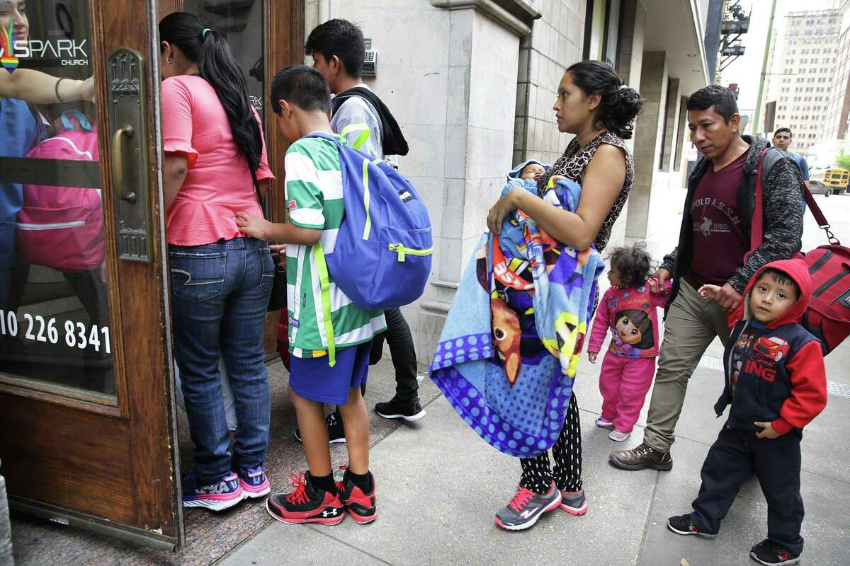 A group of migrants released from a Texas detention center is lead into Travis Park Methodist Church after being dropped off by a Homeland Securty bus on Friday, March 29, 2019, at the San Antonio bus station.