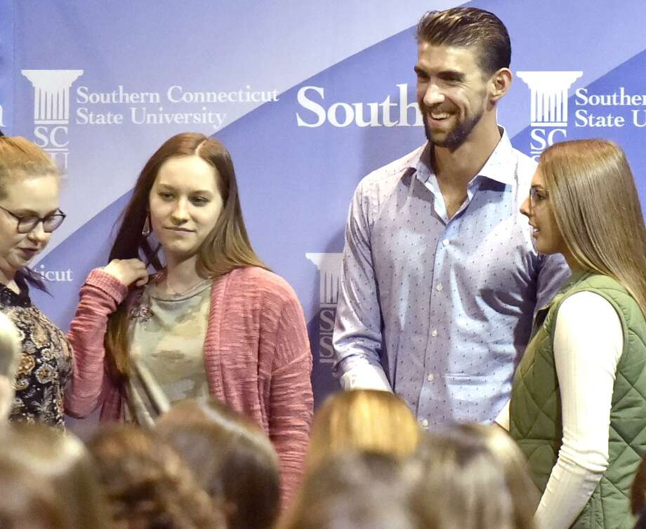 Swimmer Michael Phelps, the most decorated Olympian in history with 28 medals and a mental health advocate, third from left, spends some time with Southern Connecticut State University students before walking on stage for his appearance at the Mary and Louis Fusco Distinguished Lecture Friday night at SCSU's Lyman Center for the Performing Arts, where he discusses his career and his challenges with depression and anxiety. Photo: Peter Hvizdak / Hearst Connecticut Media / New Haven Register