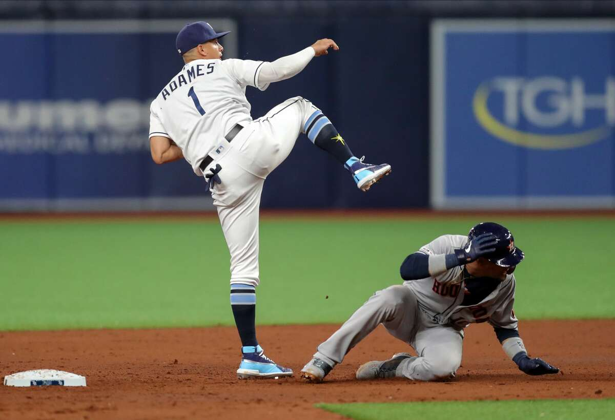 ST. PETERSBURG, FL - MARCH 29: Willy Adames #1 of the Tampa Bay Rays follows through on a throw over Yuli Gurriel #10 of the Houston Astros to complete a double play in the sixth inning of a baseball game at Tropicana Field on March 29, 2019 in St. Petersburg, Florida. (Photo by Mike Carlson/Getty Images)