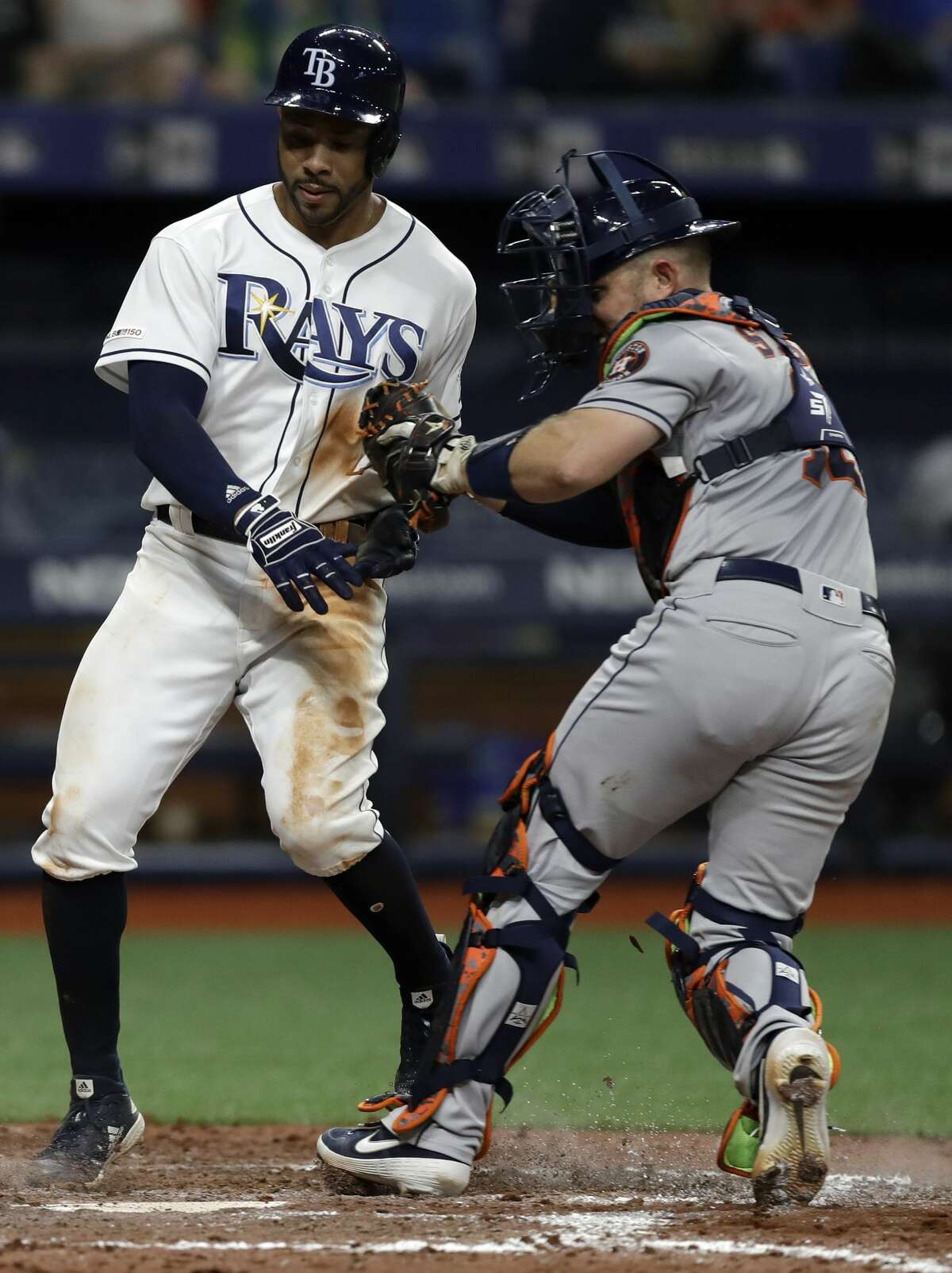 Houston Astros catcher Max Stassi, right, tags out Tampa Bay Rays' Tommy Pham after Pham tried to score on an infield single by Avisail Garcia during the eighth inning of a baseball game Friday, March 29, 2019, in St. Petersburg, Fla. (AP Photo/Chris O'Meara)