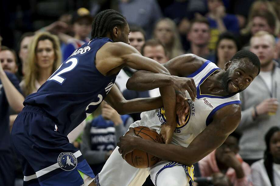 Warriors forward Draymond Green fights for possession with Andrew Wiggins during the second half Friday in Minnesota . Photo: Stacy Bengs / Associated Press