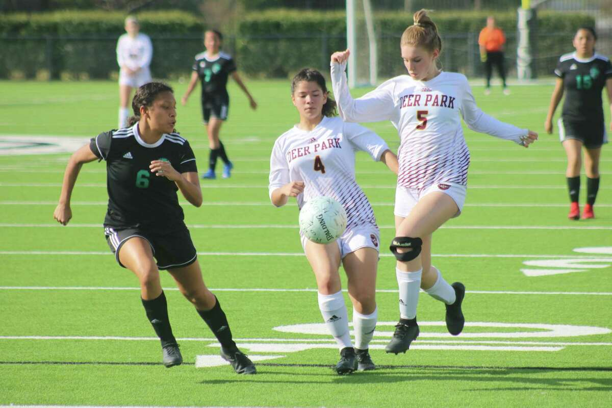 Mariana Alvarez-Garcia (4) and Camden Chance work to keep the ball away from a nearby Lady Maverick during Friday night's bi-district victory for the Lady Deer.