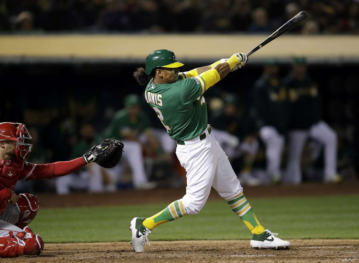 Oakland Athletics' Khris Davis swings for a two-run home run off Los Angeles Angels' Matt Harvey during the sixth inning of a baseball game Friday, March 29, 2019, in Oakland, Calif. (AP Photo/Ben Margot)