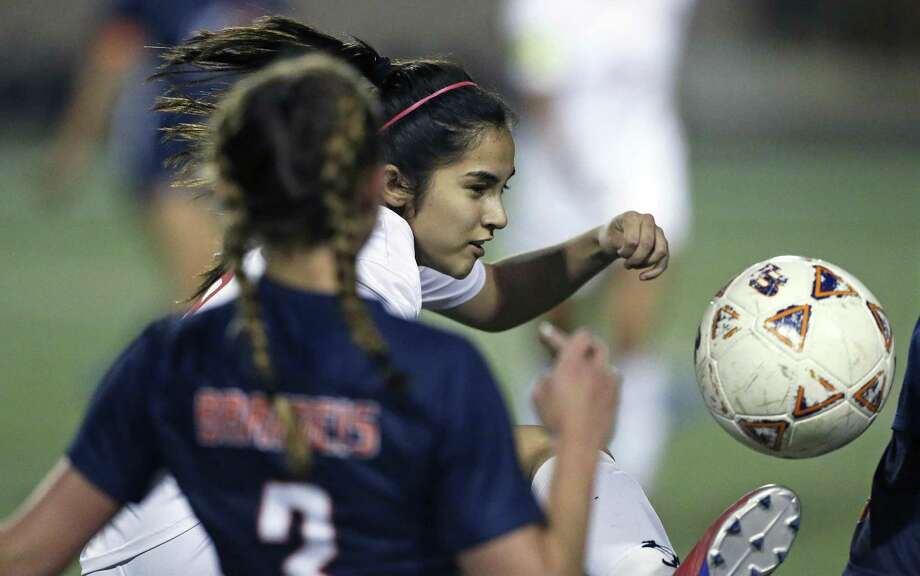 The Volunteer's Victoria Castanon slips a pass through defenders as LEE plays Brandeis in girls 6A bidistrict soccer at Farris Stadium on March 29, 2019. Photo: Tom Reel, Staff / Staff Photographer / 2019 SAN ANTONIO EXPRESS-NEWS