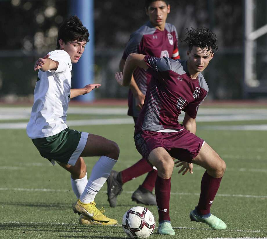 Reagan's Emi Alcantara, left, and the Ram's Ahmed Jzee vie for control on the turf as Reagan plays Marshall in boys 6A bidistrict soccer at Farris Stadium on March 29, 2019. Photo: Tom Reel, Staff / Staff Photographer / 2019 SAN ANTONIO EXPRESS-NEWS