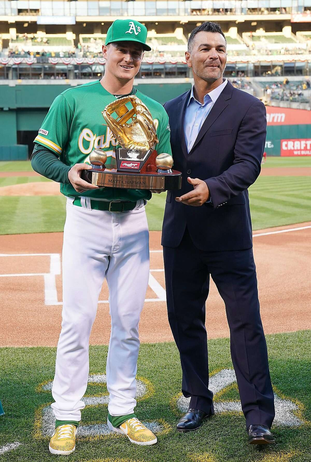 OAKLAND, CA - MARCH 29: Matt Chapman #26 of the Oakland Athletics is presented with his Rawlings 2018 Gold Glove Award by former Oakland Athletics gold glover Eric Chavez prior to the start of his game against the Los Angeles Angels of Anaheim at Oakland-Alameda County Coliseum on March 29, 2019 in Oakland, California. (Photo by Thearon W. Henderson/Getty Images)