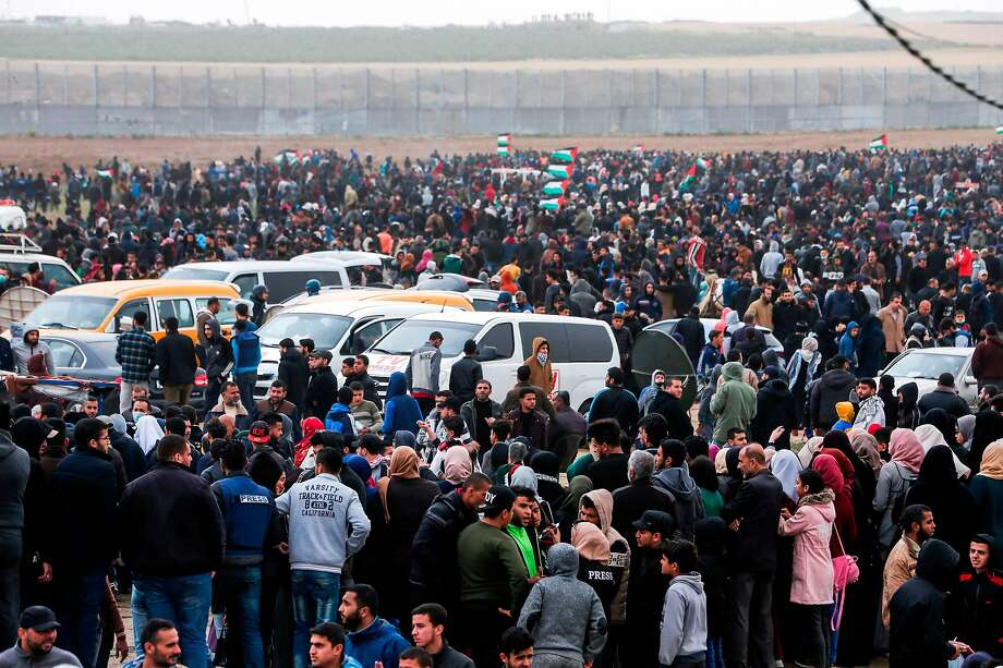 """Palestinians gather during a demonstration near the border with Israel in Malaka east of Gaza City on March 30, 2019, as Palestinians mark the first anniversary of the """"March of Return"""" border protests. - This marks the first anniversary of the often violent weekly border demonstrations in which around 200 Palestinians and an Israeli soldier have been killed, coming just 10 days before a keenly contested general election in Israel. The border protests peaked in May 2018, when Israeli forces shot dead at least 62 Palestinians in a single day in clashes over the transfer of the US embassy to Israel to the disputed city of Jerusalem. (Photo by MAHMUD HAMS / AFP)MAHMUD HAMS/AFP/Getty Images Photo: Mahmud Hams / AFP / Getty Images"""
