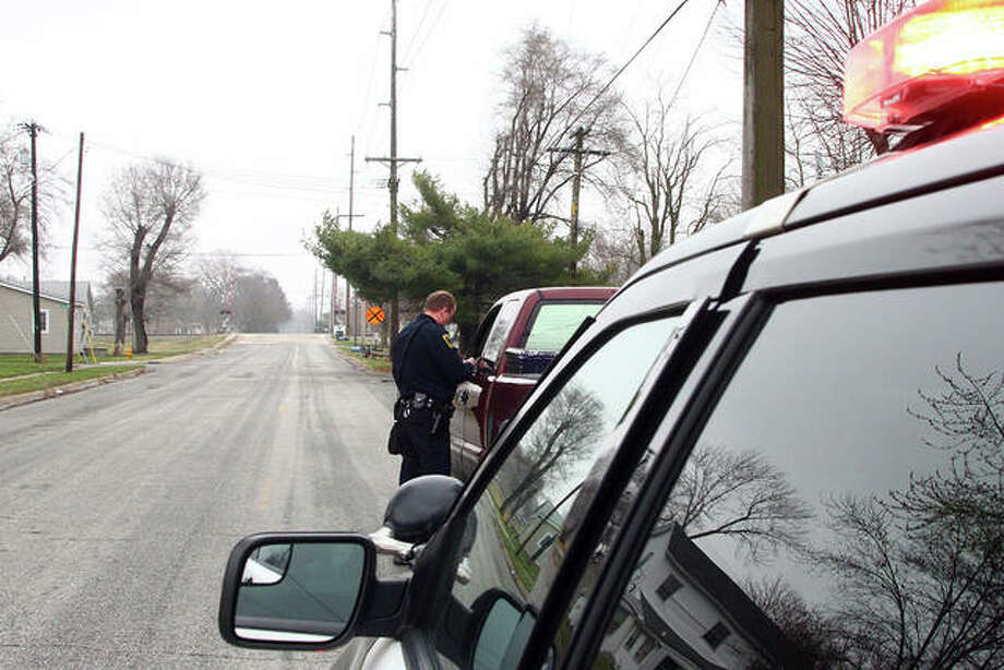 Jacksonville Patrolman Brock Lewis initiates a traffic stop Friday in Jacksonville. Lewis positions his vehicle during traffic stops so that other traffic must go around, giving him space to approach the driver that has been pulled over. Photo: Rosalind Essig | Journal-Courier