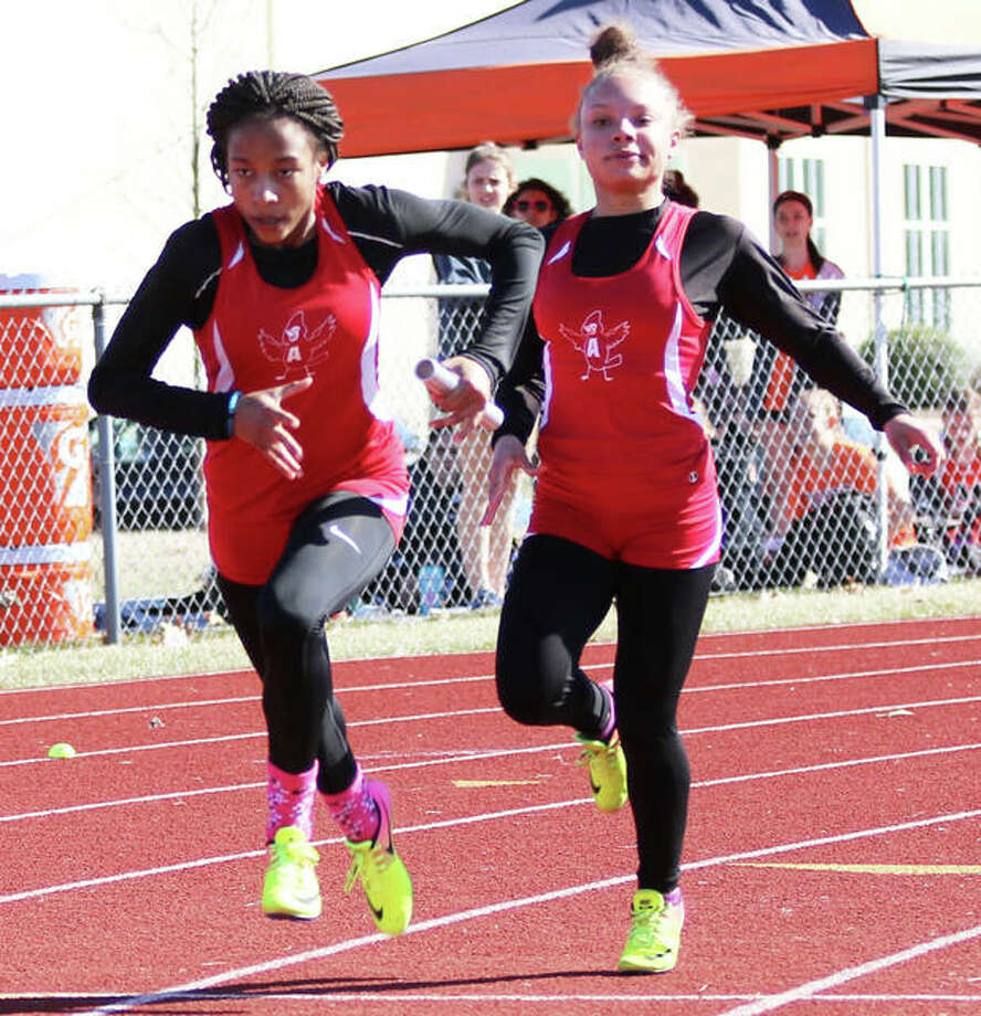 Alton's Renee Raglin (left) takes the baton from Jeanea Epps on the first first exchange for the Redbirds' 4x100 relay on March 22 at the Southwestern Illinois Relays in Edwardsdville. The Redbirds were at the Belleville West Invite on Friday and turned in a fifth-place finish in the 4x100.