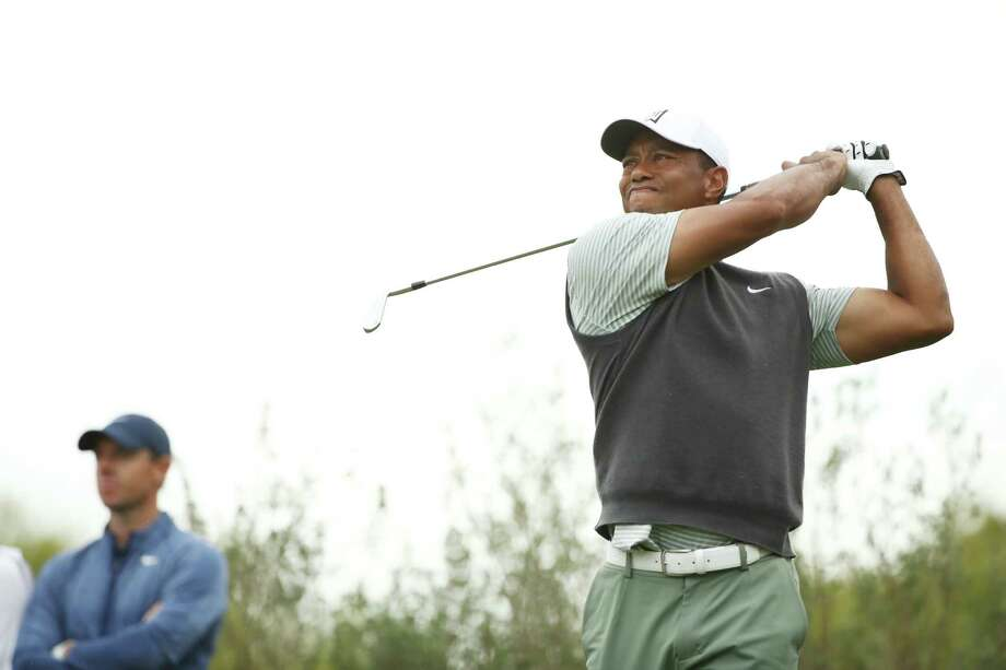 AUSTIN, TEXAS - MARCH 30: Tiger Woods of the United States plays his shot from the 11th tee as Rory McIlroy of Northern Ireland looks on during the fourth round of the World Golf Championships-Dell Technologies Match Play at Austin Country Club on March 30, 2019 in Austin, Texas. Photo: Ezra Shaw, Getty Images / 2019 Getty Images