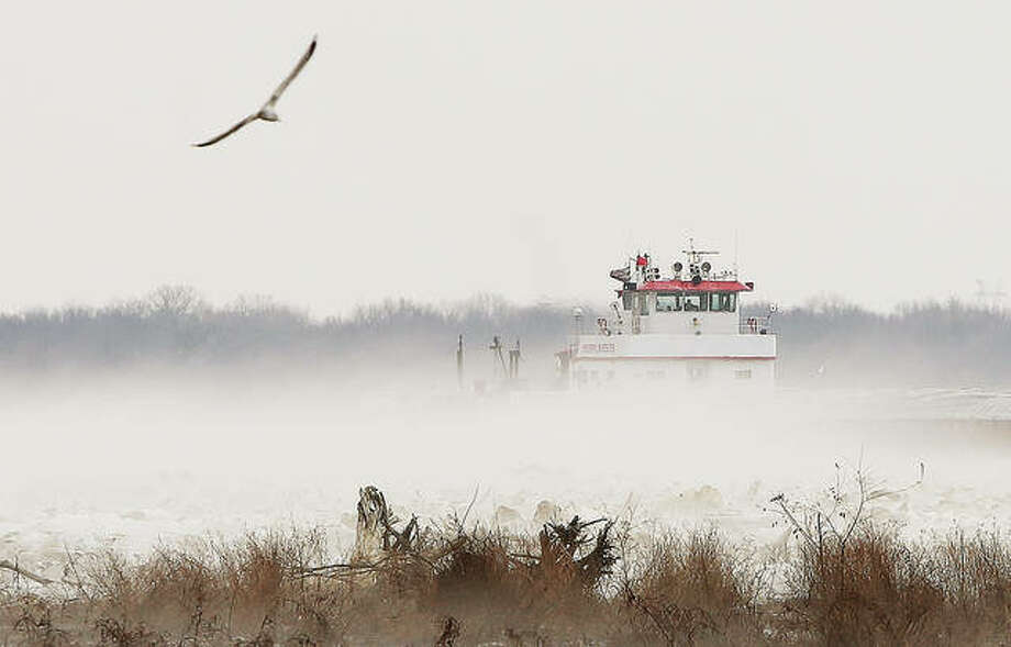 A towboat and barges push upstream through an erie looking fog near the Alton Marina.