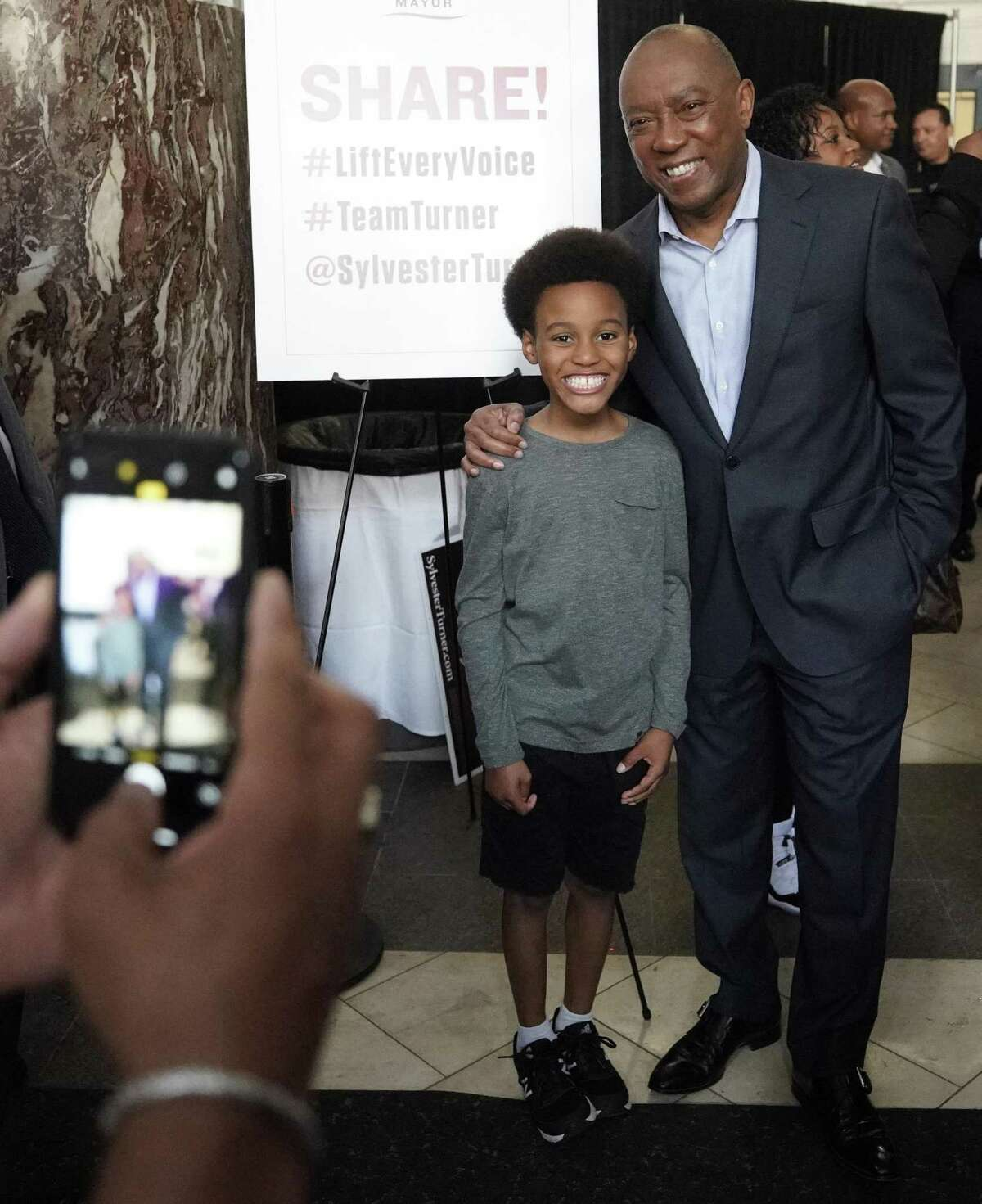 Houston mayor Sylvester Turner poses with Paul Cannings III, 9, as he greets supporters during his kick off mayoral re-election campaign event held at Union Station in Minute Maid Park Saturday, March 30, 2019, in Houston.