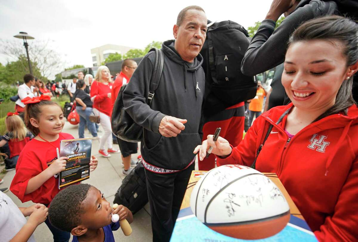Coach Kelvin Sampson autographed a basketball for Krystal Aguilar, right, as fans greet the University of Houston men's basketball team as they return to the campus Saturday, March 30, 2019, in Houston. The team lost 62-58 to Kentucky in the NCAA Midwest Regional in Kansas City on Friday.
