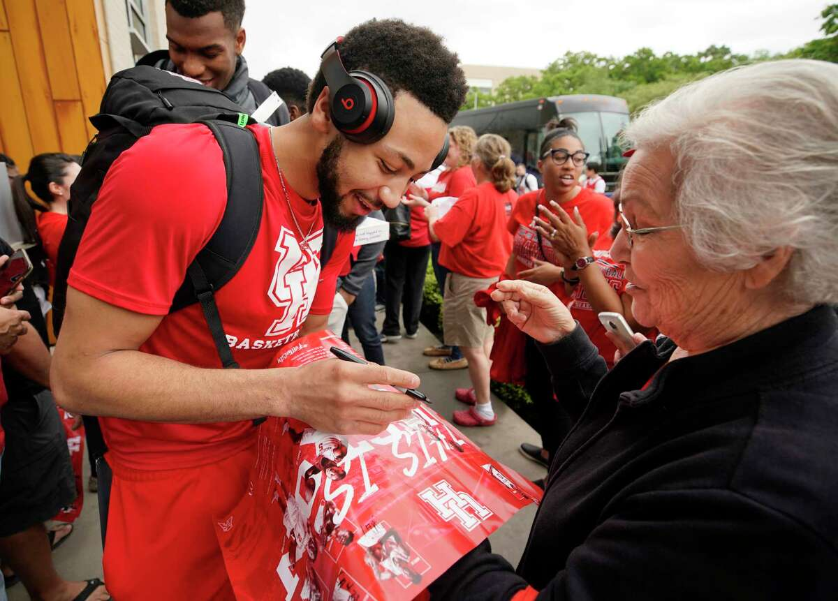 Player Galen Robinson Jr. signs a poster for Juanita C. Lopez as fans greet the University of Houston men's basketball team as they return to the campus Saturday, March 30, 2019, in Houston. The team lost 62-58 to Kentucky in the NCAA Midwest Regional in Kansas City on Friday.