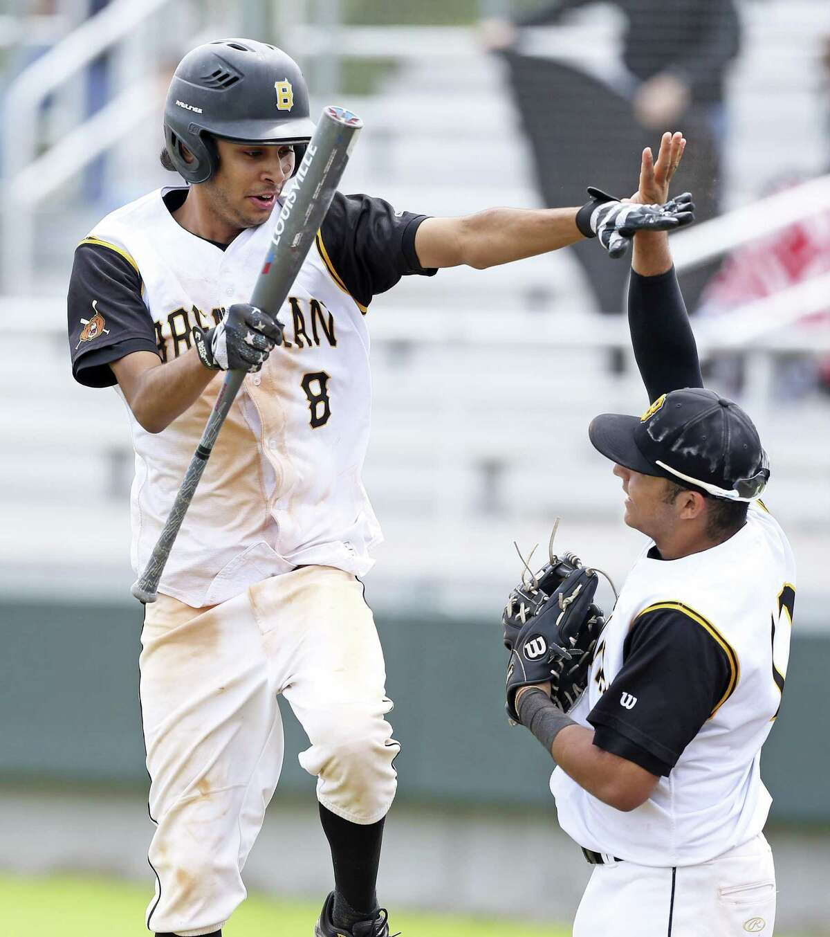 Esteban Gonzales leaps for a high five after scoring in the game ending sixth inning as Brennan beats Jay 10-0 in District 28-6A baseball at Northside Field 1 on March 30, 2019.