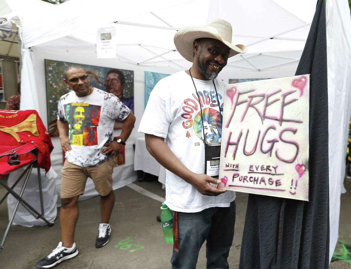 A sign offering free hugs with every purchase of artwork at Rodney Butler's booth during the Bayou City Art Festival in Memorial Park, Saturday, March 30, 2019, in Houston. In it's 48th year, there are more than 300 artists showcasing their work, and as one of the nation's premier outdoor fine art events, the three-day festival ends Sunday, and will be open from 10am-6pm. The festival benefits local nonprofit partners and features live music, local food vendors and food trucks, beverages, entertainment, a Children's Creative Zone and more.