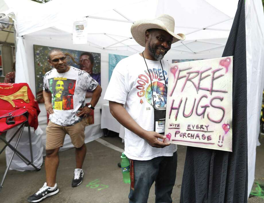 A sign offering free hugs with every purchase of artwork at Rodney Butler's booth during the Bayou City Art Festival in Memorial Park, Saturday, March 30, 2019, in Houston. In it's 48th year, there are more than 300 artists showcasing their work, and as one of the nation's premier outdoor fine art events, the three-day festival ends Sunday, and will be open from 10am-6pm. The festival benefits local nonprofit partners and features live music, local food vendors and food trucks, beverages, entertainment, a Children's Creative Zone and more. Photo: Karen Warren, Houston Chronicle / Staff Photographer / © 2019 Houston Chronicle
