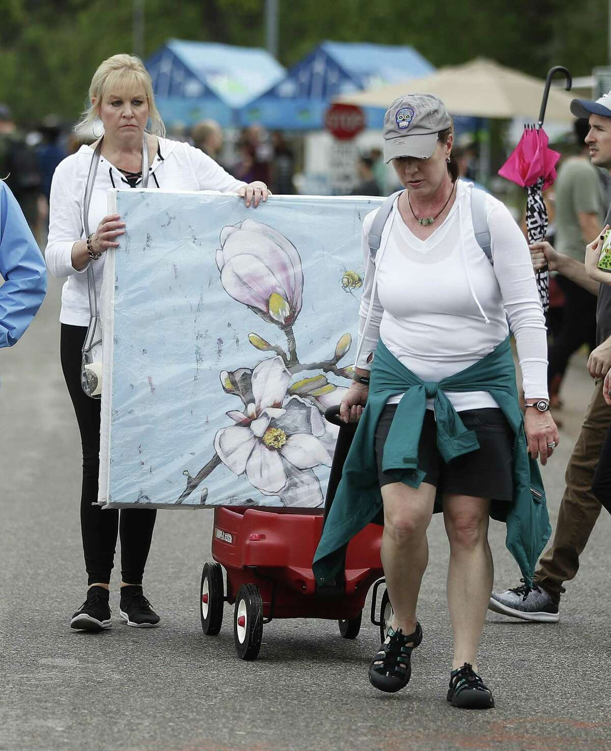 Laurie Pleasant carts out her art with the help of her friend Cindy Cameron during the Bayou City Art Festival in Memorial Park, Saturday, March 30, 2019, in Houston. In it's 48th year, there are more than 300 artists showcasing their work, and as one of the nation's premier outdoor fine art events, the three-day festival ends Sunday, and will be open from 10am-6pm. The festival benefits local nonprofit partners and features live music, local food vendors and food trucks, beverages, entertainment, a Children's Creative Zone and more.