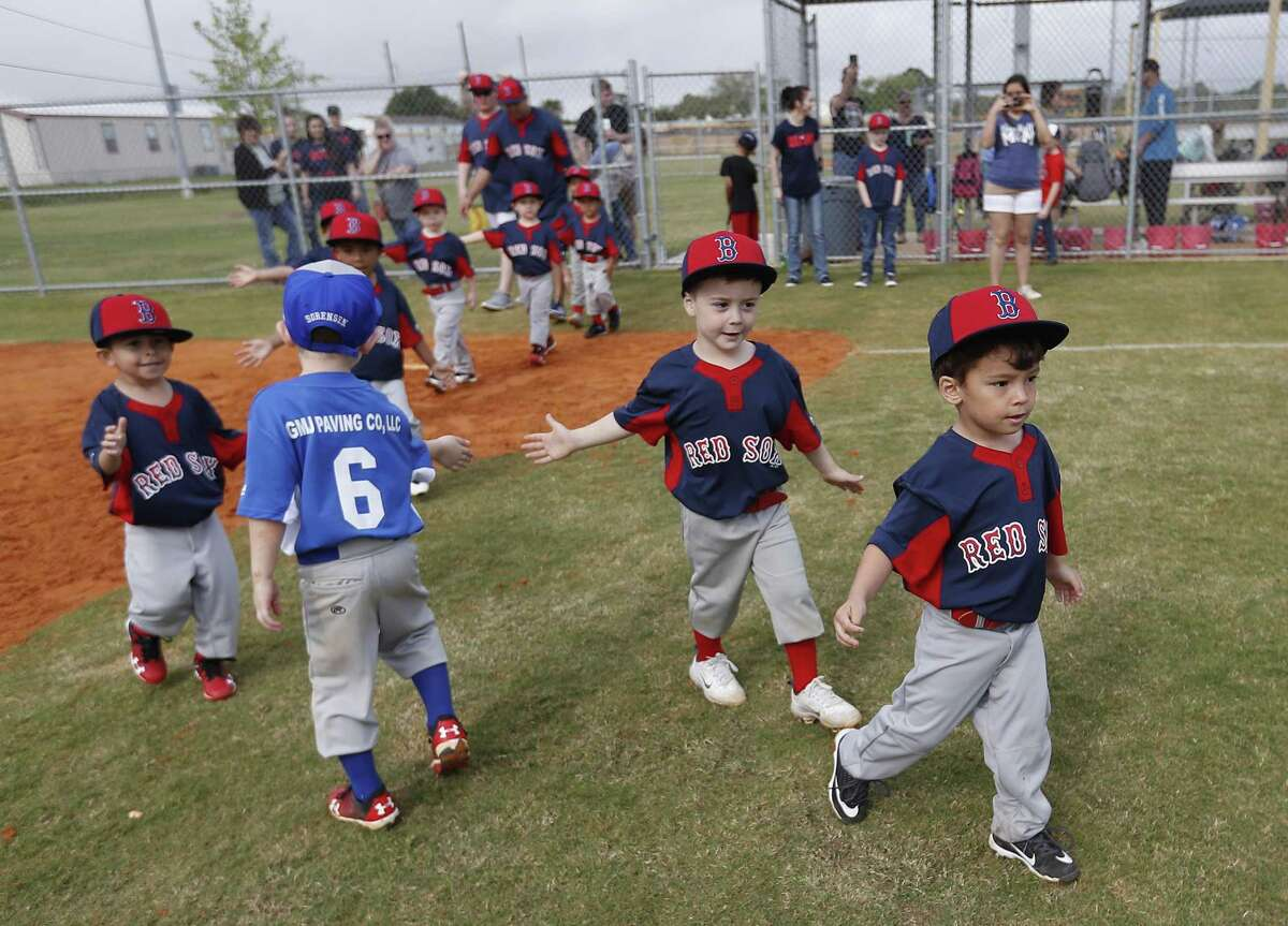 Members of the Red Sox and L.A. Dodgers teams high-five each other after their game during Deer Park PONY baseball games at Spencerview Athletic Complex, Saturday, March 30, 2019, in Deer Park. First the Deer Park PONY baseball league had to cancel games because of bad weather. Then came the ITC chemical fire, which cancelled another full week of games and Opening Day.