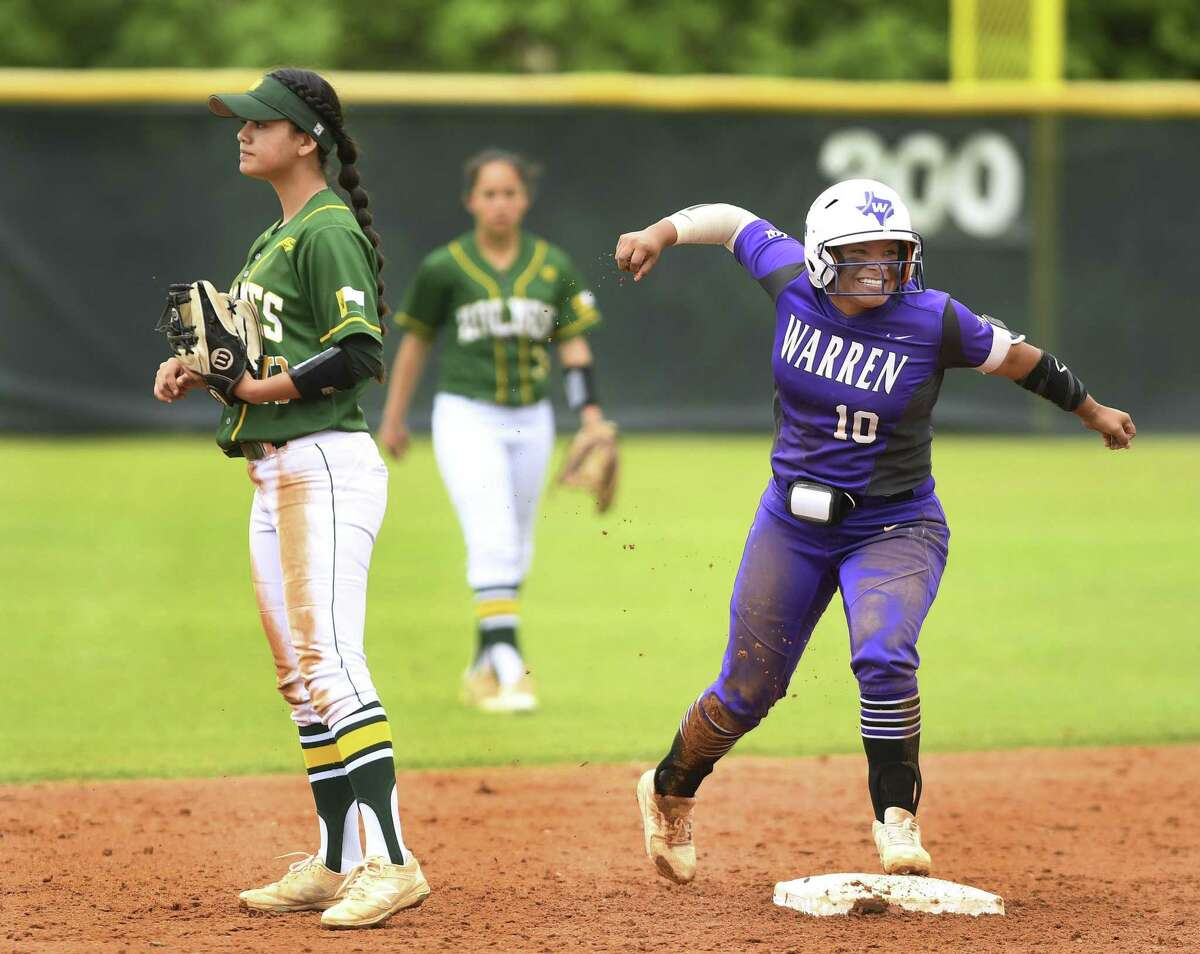 Lauryn Hernandez of Warren High celebrates by Holmes second baseman Lauren Olivarri after hitting a double during District 28-6A softball action at the Northside ISD Sports Complex on Saturday, March 30, 2019. Warren won, 3-0.