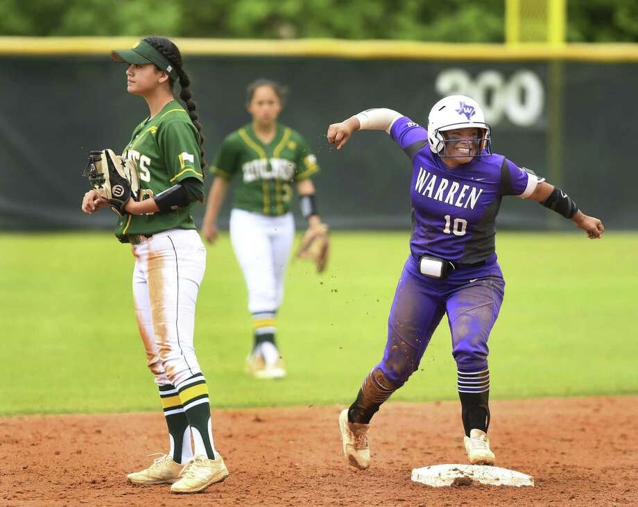 Lauryn Hernandez of Warren High celebrates by Holmes second baseman Lauren Olivarri after hitting a double during District 28-6A softball action at the Northside ISD Sports Complex on Saturday, March 30, 2019. Warren won, 3-0. Photo: Billy Calzada / Staff Photographer / San Antonio Express-News
