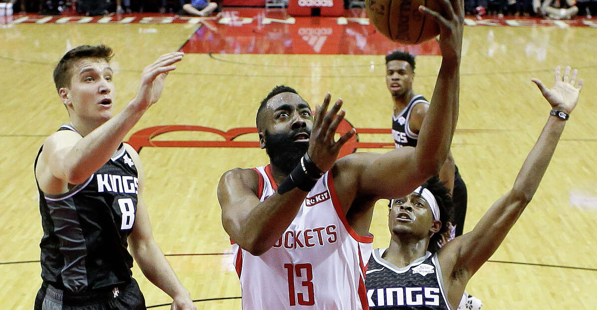Houston Rockets guard James Harden (13) drives to the basket as Sacramento Kings guard Bogdan Bogdanovic (8) and guard De'Aaron Fox defend during the first half of an NBA basketball game, Saturday, March 30, 2019, in Houston. (AP Photo/Eric Christian Smith)