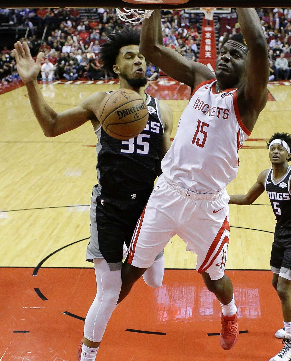 Houston Rockets center Clint Capela (15) dunks as Sacramento Kings forward Marvin Bagley III defends during the first half of an NBA basketball game, Saturday, March 30, 2019, in Houston. (AP Photo/Eric Christian Smith)