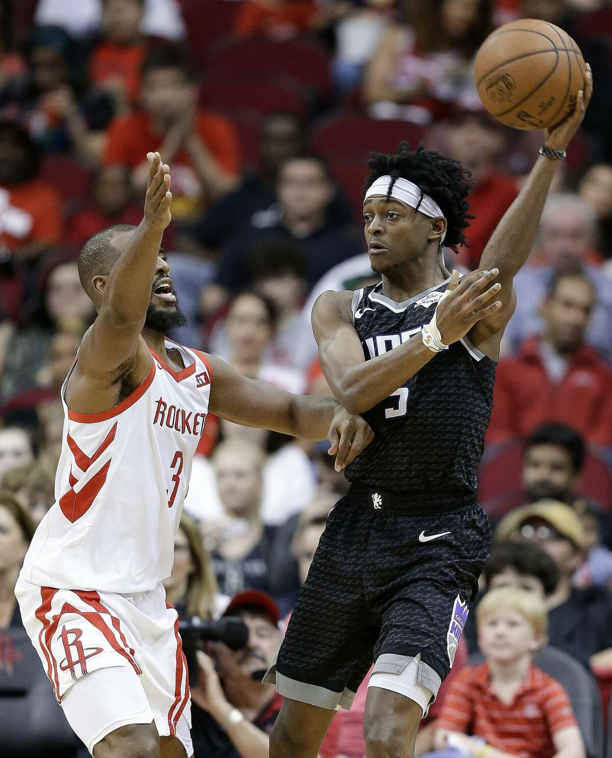 Sacramento Kings guard De'Aaron Fox, right, passes the ball as Houston Rockets guard Chris Paul defends during the second half of an NBA basketball game Saturday, March 30, 2019, in Houston. Houston won 119-108. (AP Photo/Eric Christian Smith)