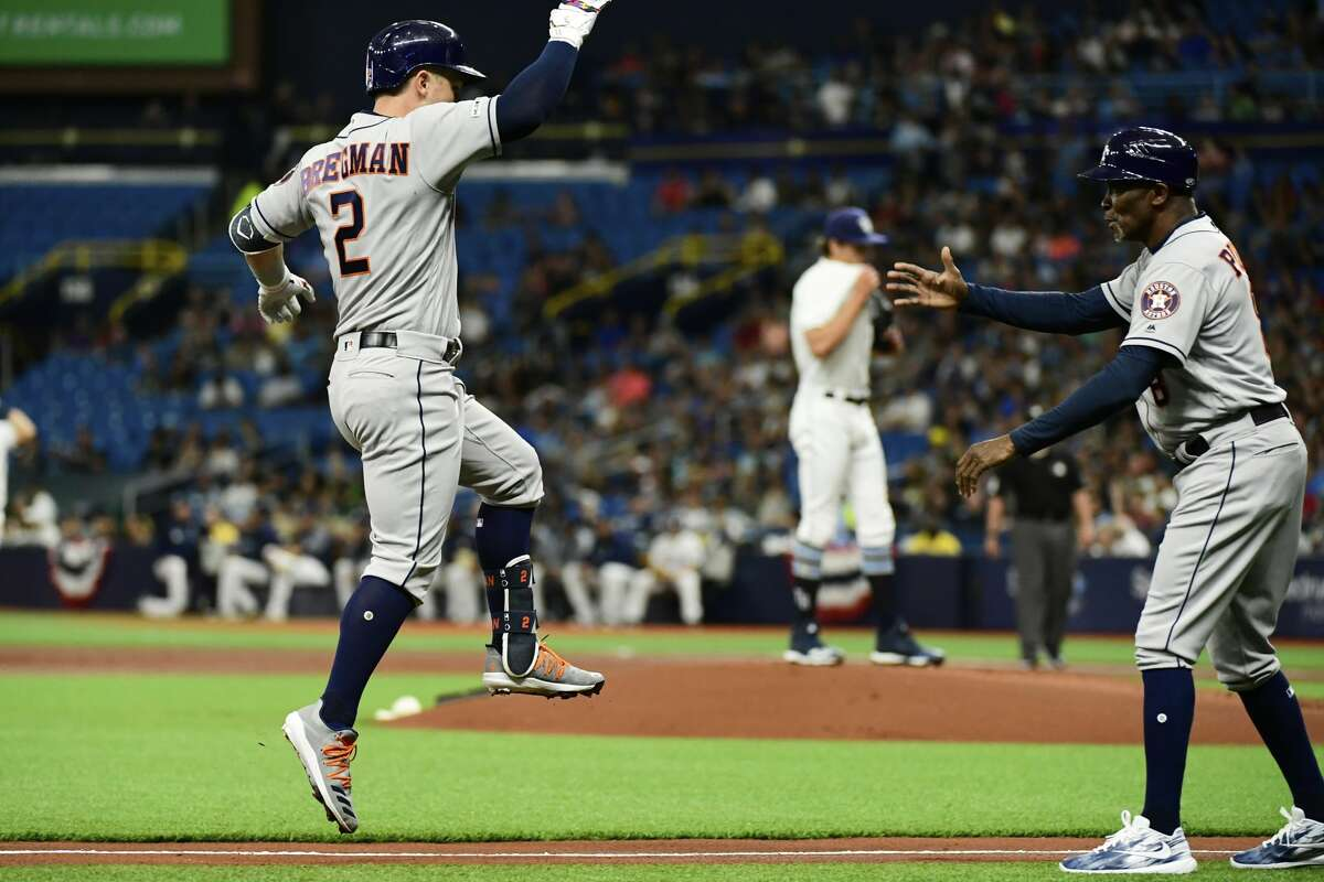 ST PETERSBURG, FLORIDA - MARCH 30: Alex Bregman #2 and Gary Pettis #8 of the Houston Astros celebrate after Bregman hit a homer off of Tyler Glasnow #20 of the Tampa Bay Rays in the first inning at Tropicana Field on March 30, 2019 in St Petersburg, Florida. (Photo by Julio Aguilar/Getty Images)