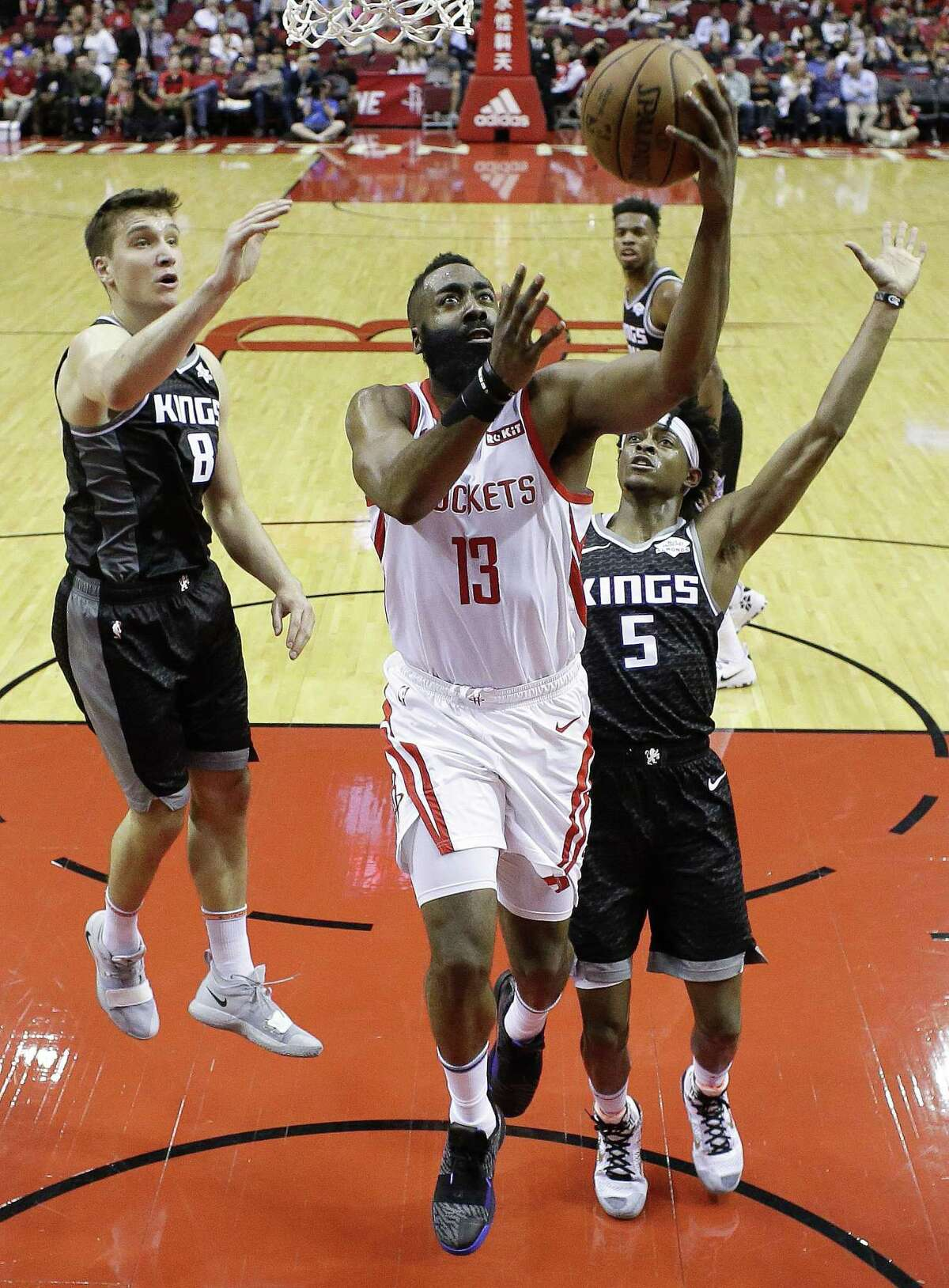 Rockets guard James Harden splits the Kings' defense on his way to 50 points. Harden filled out his triple-double with 11 rebounds and 10 assists. He was 17-for-18 from the free-throw line.