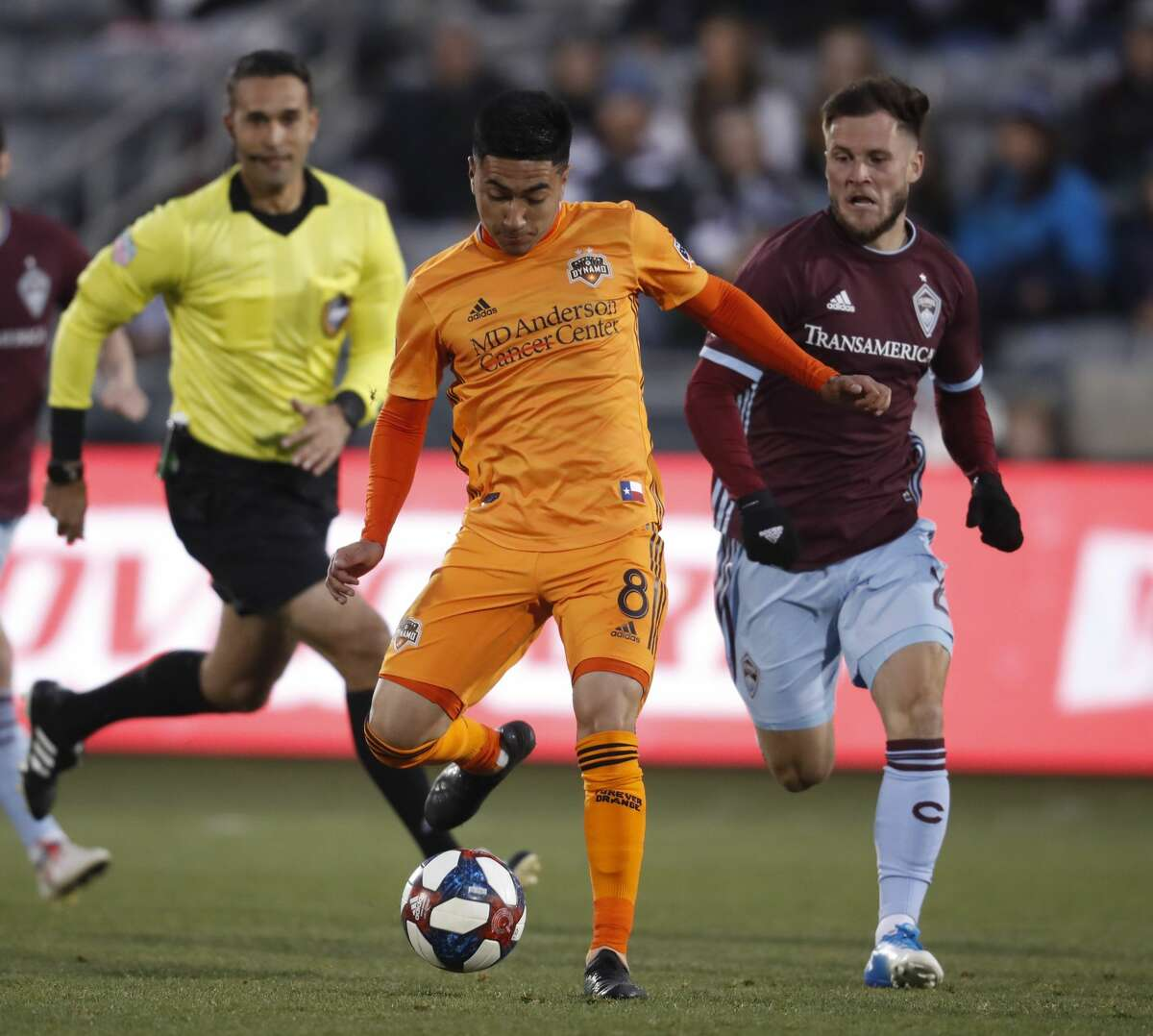 Houston Dynamo midfielder Memo Rodriguez, center, passes the ball as Colorado Rapids defender Keegan Rosenberry, right, pursues in the first half of a MLS soccer match Saturday, March 30, 2019, in Commerce City, Colo. (AP Photo/David Zalubowski)