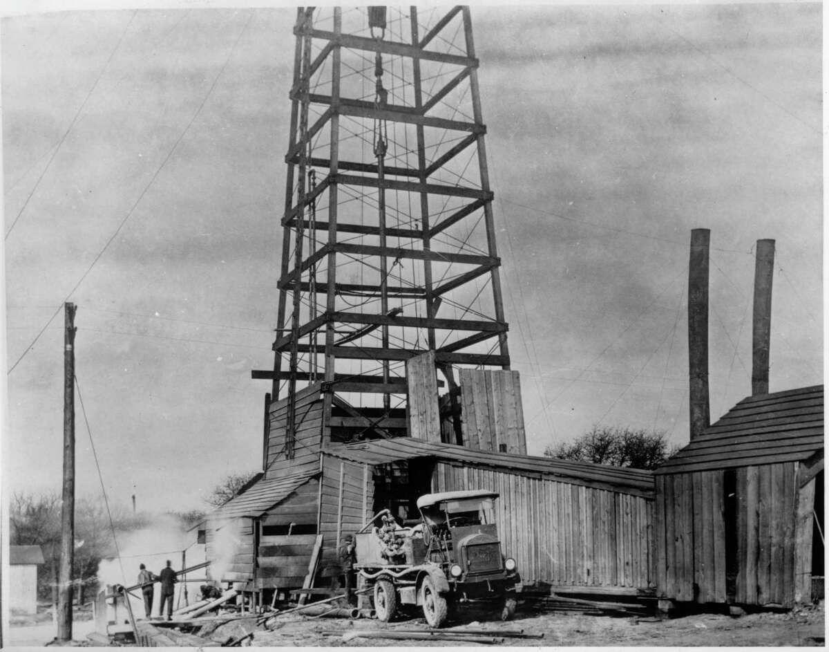 Since 1919, the Railroad Commission has regulated energy in Texas. Here, a Halliburton truck parks at a wooden oil derrick in the '20s.