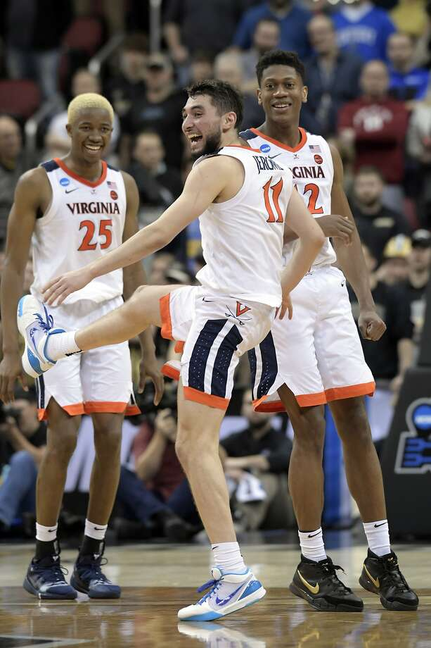 Virginia's Ty Jerome (11) celebrates with teammates Mamadi Diakite (25) and De'Andre Hunter (12) after defeating Purdue. Photo: Timothy D. Easley / Associated Press