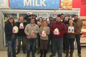 Pike-Scott Farm Bureau Young Leaders Christian Dean (from left), Brock Willard, Elijah Hoover, Wyatt Bradshaw, Marlee Jo Schultz, Payton Mckinnon, John Schultz, Mark McQueen, Josh Moffit, Rachel Smith, and Jesse Poor stand with milk at Save-A-Lot in Pittsfield.