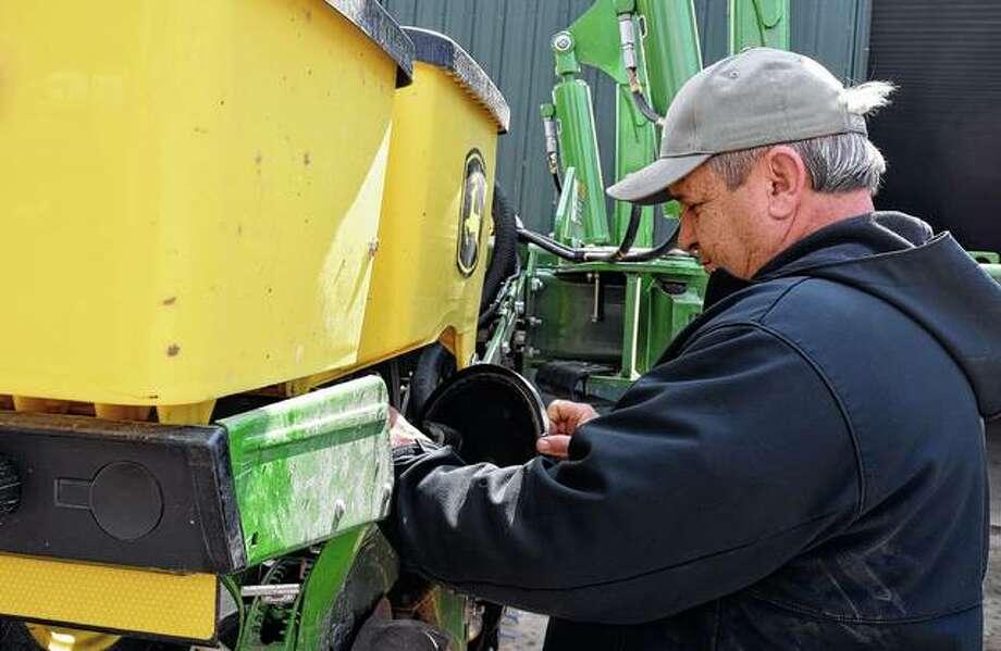 Dale Hadden checks his planter in preparation for the season.