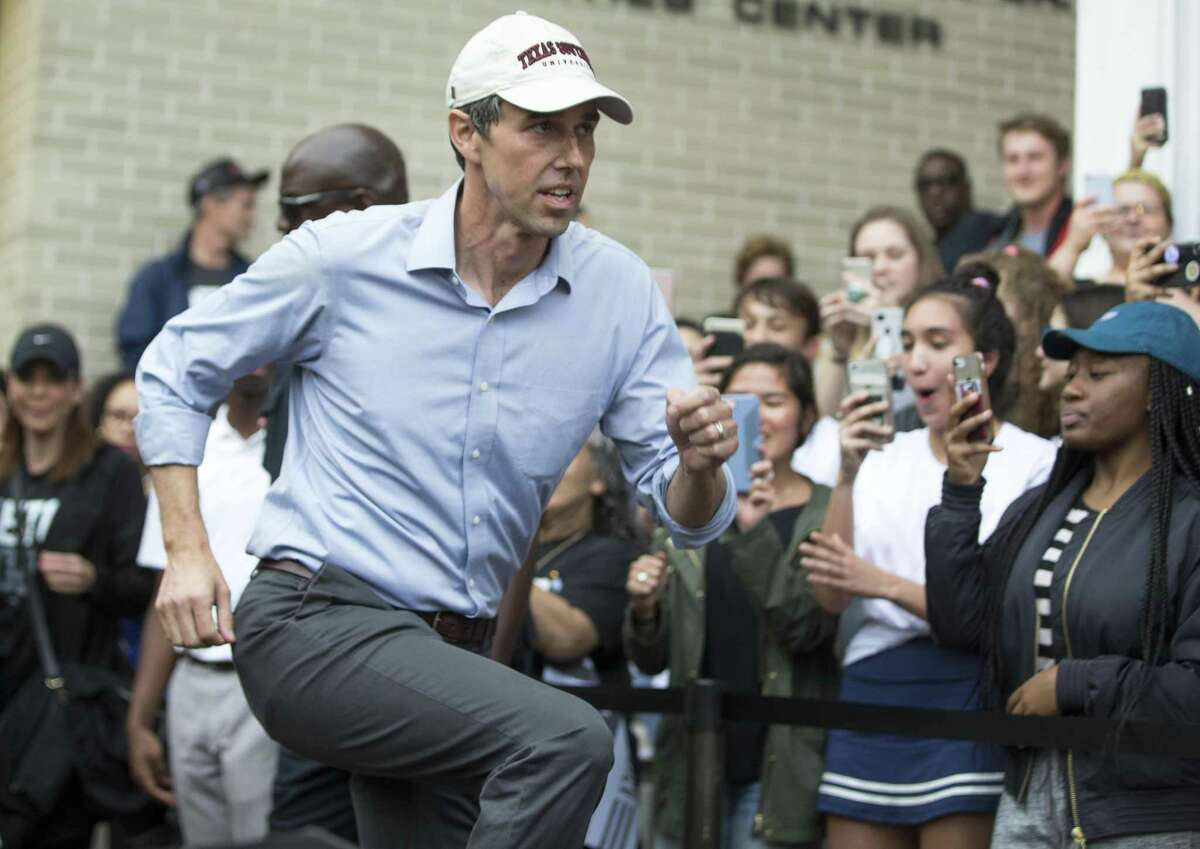 Democratic presidential hopeful Beto O'Rourke hops up onto the stage as he arrives to speak to his supporters at Texas Southern University, one stop in part of his three-city official campaign kickoff in Houston on Saturday.