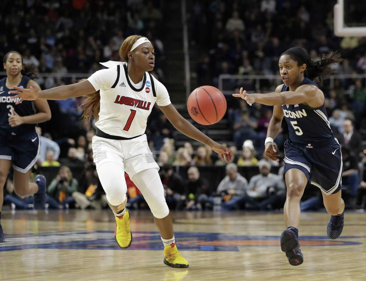 UConn guard Crystal Dangerfield (5) passes around Louisville guard Dana Evans (1) during the first half of a regional championship final in the NCAA women's college basketball tournament Sunday in Albany, N.Y.