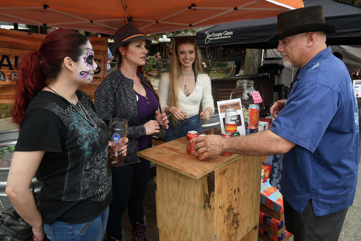 Leslie Reyna, from left, Chrissy Bernal, and Chrissy's daughter Sierra, 20, serve customer Dean Zaino, of Cypress, while working the Brautigams BarNGrill (in Tomball) booth during the Tomball German Heritage Festival at the Tomball Depot on March 30, 2019.