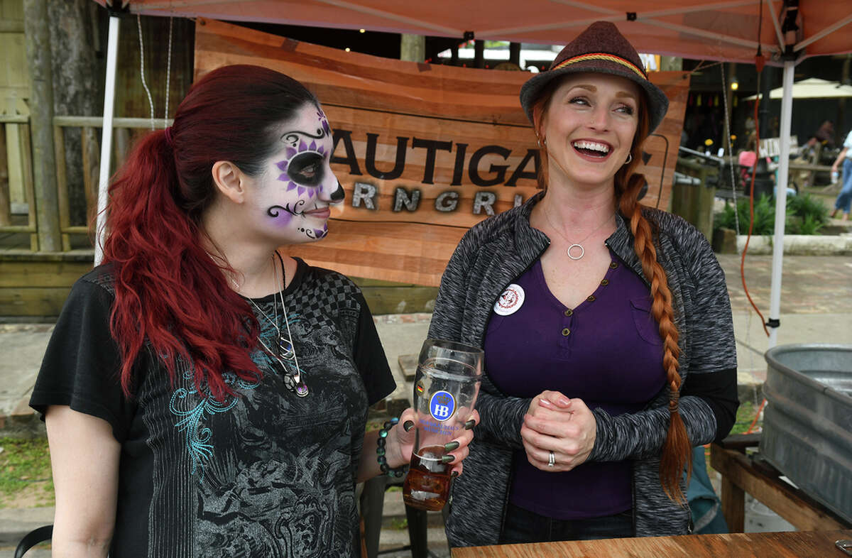 Leslie Reyna, from left, and Chrissy Bernal entertain their customers while working the Brautigams BarNGrill (in Tomball) booth during the Tomball German Heritage Festival at the Tomball Depot on March 30, 2019.