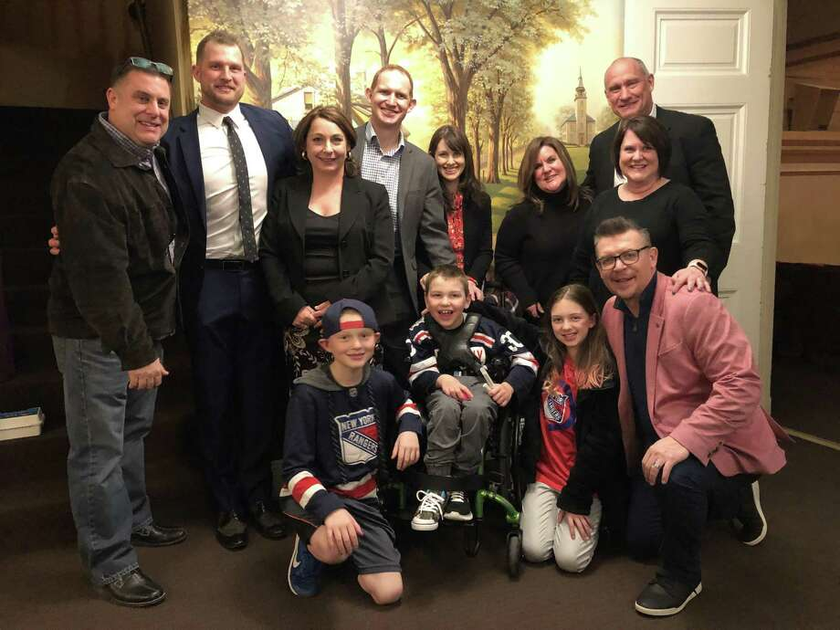 Former NHL All-Star Theo Fleury spoke to help raise money for medical research of an extremely rare brain disease during a recent visit to the Ridgefield Playhouse on Rare Disease Day. Bob DiTullio, Jr., left; Colton Orr (navy blazer), Racquel DiTullio, Nick Buck (grey blazer), Allison Buck, Gina Carolan, Tom Laidlaw, Lisa Lynch, James Buck, Sam Buck, center, Imogen Buck, Theo Fleury (pink blazer). Photo: / Contributed Photo