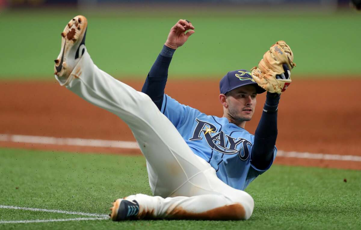 ST. PETERSBURG, FL - MARCH 31: Daniel Robertson #28 of the Tampa Bay Rays makes a catch on an attempted bunt by Jose Altuve #27 of the Houston Astros to end the game in the ninth inning of a baseball game at Tropicana Field on March 31, 2019 in St. Petersburg, Florida. (Photo by Mike Carlson/Getty Images)